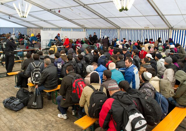 Refugees wait to be registered in a service tent at the train station in the Bavarian city of Passau, southern Germany, Monday, Nov. 2, 2015.