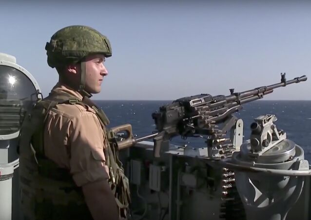 In this photo made from the footage taken from Russian Defense Ministry official web site on Friday, Nov. 27, 2015, a Russian seaman stands next to a machine gun on the Russian missile cruiser Moskva, near the shore of Syria's province of Latakia, Syria