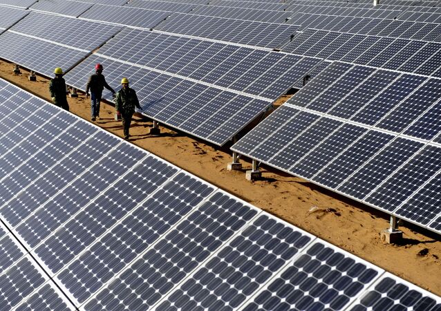 Workers check solar panels in Yulin, northwest China's Shaanxi Province, as the traditional mineral-resource-rich city turned its development on clean energy industries such as wind power or solar power