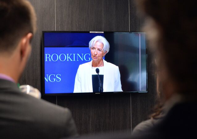 Journalists look at a live feed outside the room where the International Monetary Fund Managing Director Christine Lagarde speaks at Brookings Institute in Washington, DC on July 8, 2015.