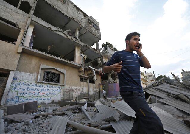 Palestinian talks on a mobile phone as he walks on the rubble of a damaged house following an overnight Israeli missile strike in Gaza City, Tuesday, July 15, 2014