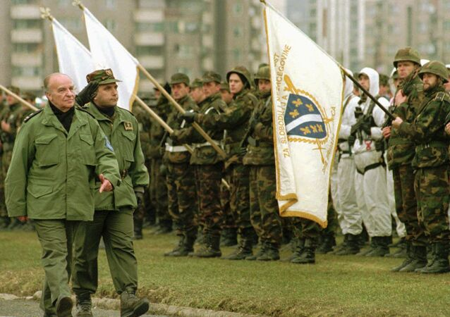 Bosnian President Alija Izetbegovic reviews troops during a military parade of the Bosnian Army in Zenica, 100 kilometres (62 miles) north of Sarajevo, Sunday December 10, 1995. Izetbegovic said that the Bosnian Army should be ready if something goes wrong during or after the NATO mandate to police the Dayton accord. At right is Bosnian Army Gen. Sakib Mahmuljin