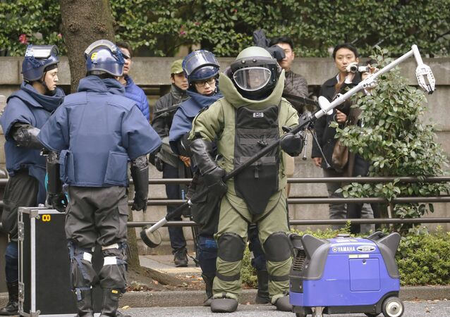 Members of a police bomb disposal squad wearing blast protection equipments prepare to work near the site of an explosion at the Yasukuni shrine in Tokyo, in this photo taken by Kyodo November 23, 2015