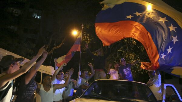 Supporters of the opposition Democratic Unity coalition wave a Venezuelan national flag from a car while they celebrate their victory on a street in Caracas December 7, 2015 - Sputnik International
