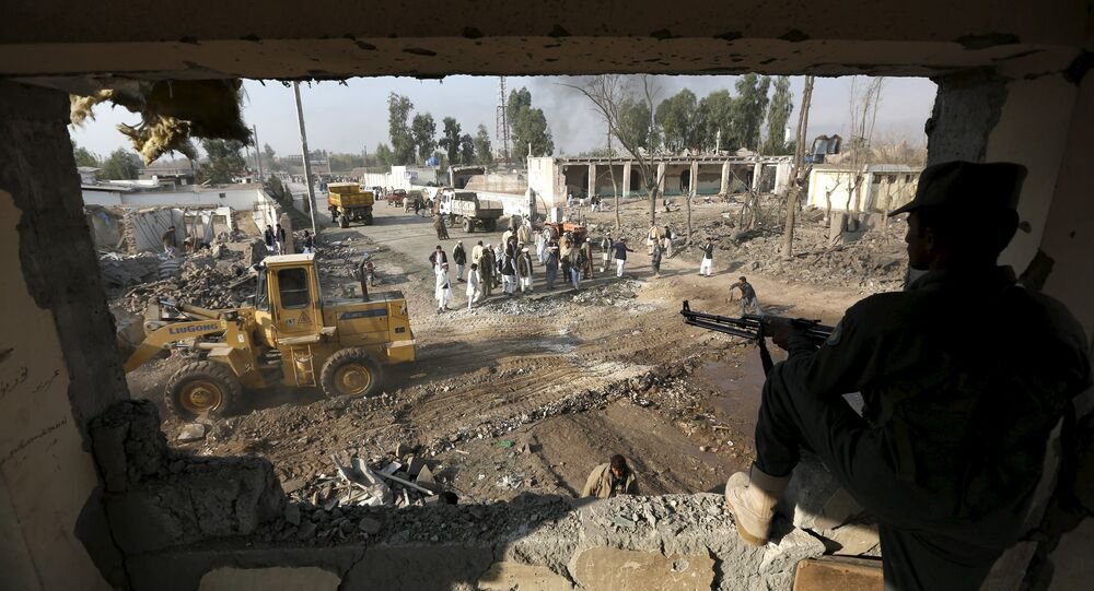 File Photo: An Afghan policeman keeps watch while men gather at the site of a suicide car bomb attack in Surkhrod district of Nangarhar province, Afghanistan, December 7, 2015