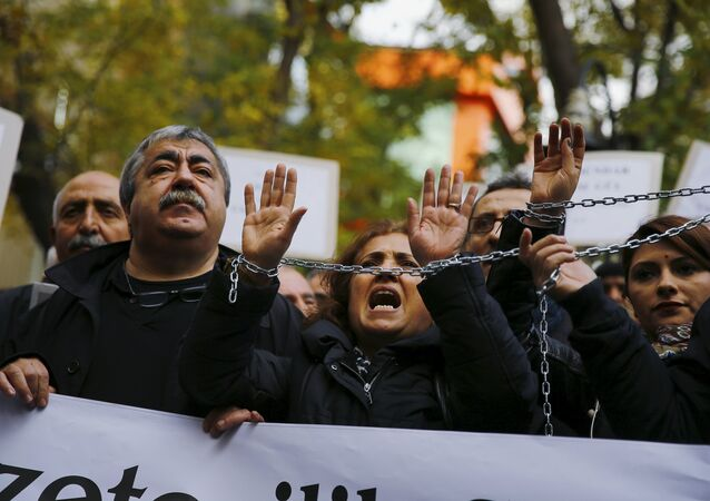 Demonstrators raise their chained hands during a protest over the arrest of journalists Can Dundar and Erdem Gul in Ankara, Turkey, November 27, 2015