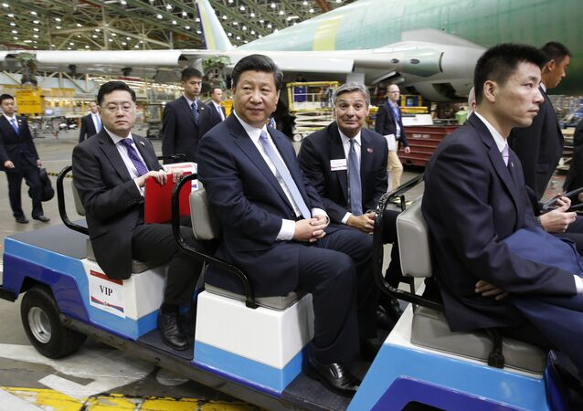 Chinese President Xi Jinping, center, and president and CEO of Boeing Commercial Airplanes, Ray Conner, tour the Boeing assembly line, Wednesday, Sept. 23, 2015 in Everett, Wash