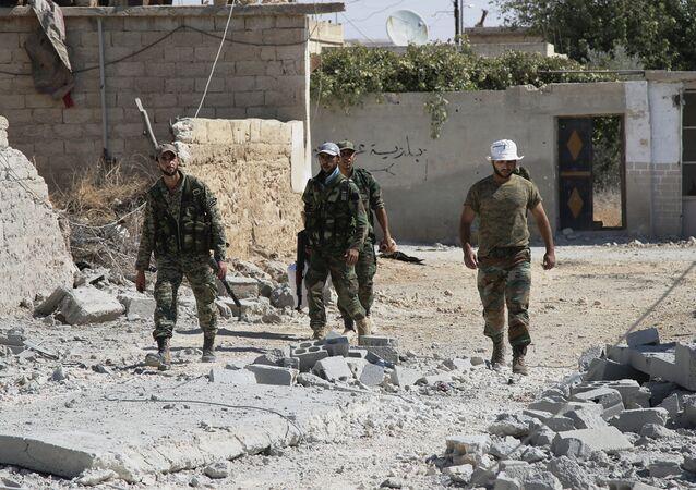 Syrian army soldiers walk in Achan, Hama province, Syria