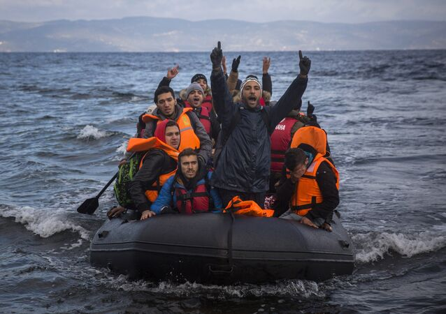 Migrants and refugees react as they arrive on a dinghy from the Turkish coast to the northeastern Greek island of Lesbos on Wednesday, Dec. 9, 2015.