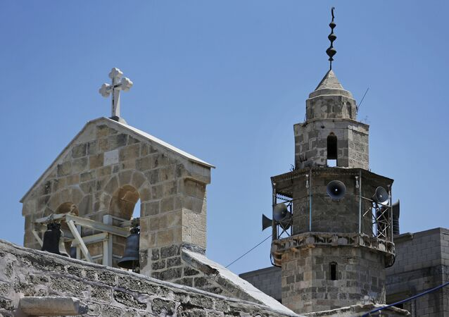 The bell tower of St. Porphyrios Greek Orthodox church, left, and the minaret of the adjacent Kateb Welaya mosque, right, are seen in Gaza City, Sunday, Aug. 10, 2014