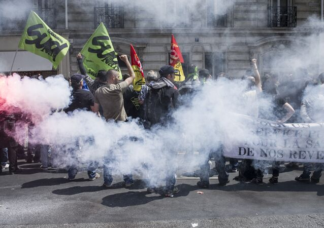 Striking workers of the French state-run rail operator SNCF, backed by French unions CGT and Sud-Rail, protest with flares during a demonstration against reform plans proposed by the French government, on June 18, 2014, at the Austerlitz train station in Paris