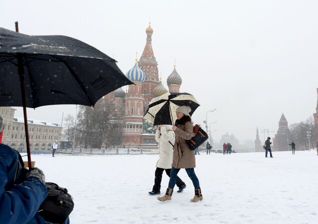 People walk during a major snowfall at the Red Square in Moscow, on January 16, 2014