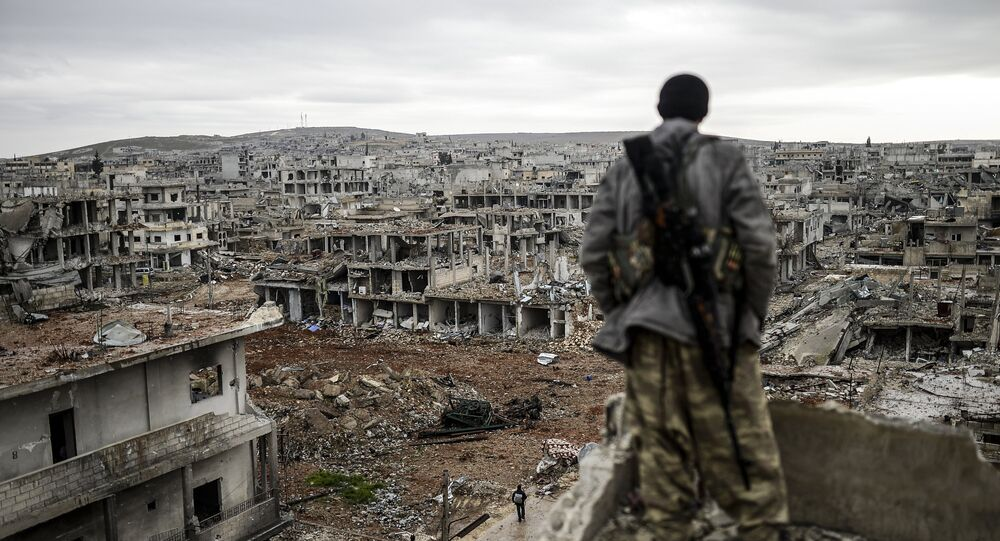 This file photo shows Musa, a 25-year-old Kurdish marksman, stands atop a building as he looks at the destroyed Syrian town of Kobane, also known as Ain al-Arab, on January 30, 2015