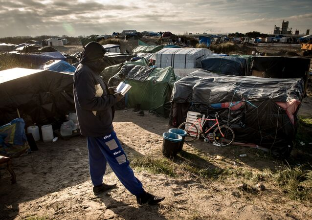 A man walks past a banner reading Pray for Deir Ezzor at the migrant camp known as the Jungle in Calais on December 7, 2015