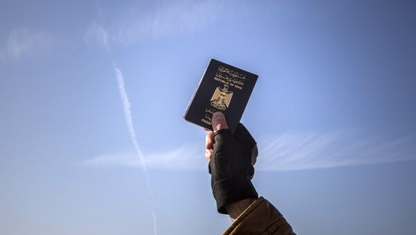 A refugee holds up his Iraqi passport at the port of Molyvos after a rescue operation by members of the Frontex, European Border Protection Agency, from Portugal near the northeastern Greek island of Lesbos, Tuesday, Dec. 8, 2015. - Sputnik International