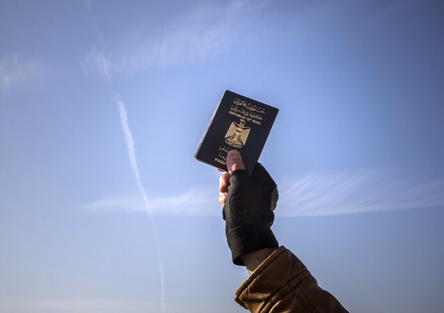 A refugee holds up his Iraqi passport at the port of Molyvos after a rescue operation by members of the Frontex, European Border Protection Agency, from Portugal near the northeastern Greek island of Lesbos, Tuesday, Dec. 8, 2015.