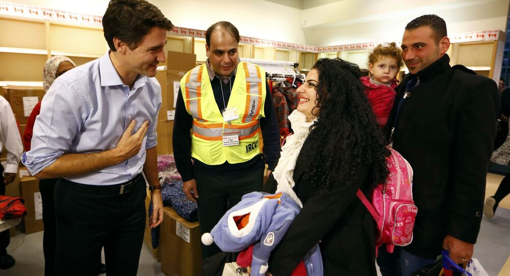 Syrian refugees are greeted by Canada's Prime Minister Justin Trudeau (L) on their arrival from Beirut at the Toronto Pearson International Airport in Mississauga, Ontario, Canada December 11, 2015