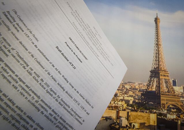 An illustration picture taken on December 10, 2015 in Paris shows a draft for the outcome of the COP21 United Nations conference on climate change next to a picture of the Eiffel Tower