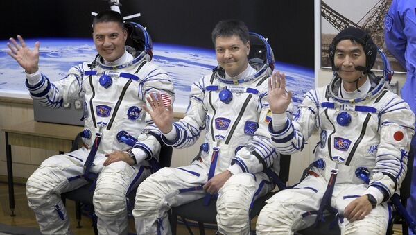 (From L) The Soyuz TMA-17M spacecraft International Space Station (ISS) crew of US astronaut Kjell Lindgren, Russian cosmonaut Oleg Kononenko and Japanese astronaut Kimiya Yui wave during a space suit testing before leaving for a launch pad of the Russian-leased Baikonur cosmodrome in Kazakhstan on July 22, 2015 a few hours before a blast off - Sputnik International