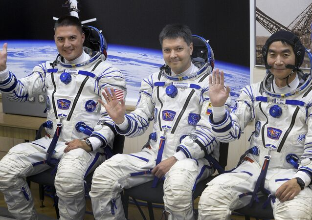 (From L) The Soyuz TMA-17M spacecraft International Space Station (ISS) crew of US astronaut Kjell Lindgren, Russian cosmonaut Oleg Kononenko and Japanese astronaut Kimiya Yui wave during a space suit testing before leaving for a launch pad of the Russian-leased Baikonur cosmodrome in Kazakhstan on July 22, 2015 a few hours before a blast off