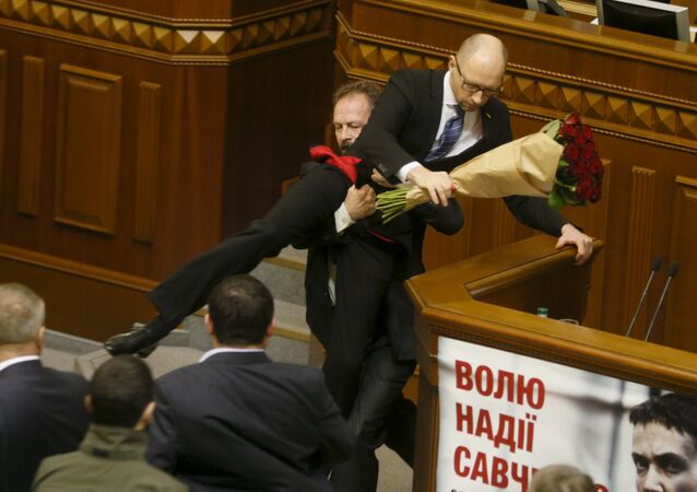 Rada deputy Oleg Barna removes Prime Minister Arseny Yatseniuk from the tribune, after presenting him a bouquet of roses, during the parliament session in Kiev, Ukraine, December 11, 2015