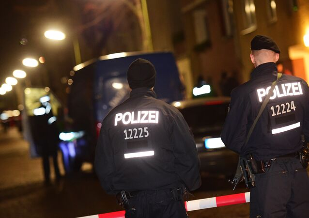 Armed police stand guard as others search a van at the scene in the Karl-Elsasser Street in Berlin's southern suburb of Britz on November 26, 2015. German police detained two suspects in a series of raids targeting Islamists in Berlin and said they were examining a suspicious object