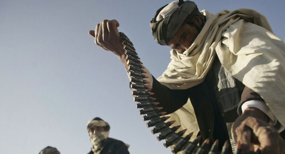 FILE - In this Dec. 28, 2011 file photo, a former Taliban fighter places a range of bullets before surrendering it to Afghan authorities, as part of a peace-reconciliation program in Herat, west of Kabul, Afghanistan
