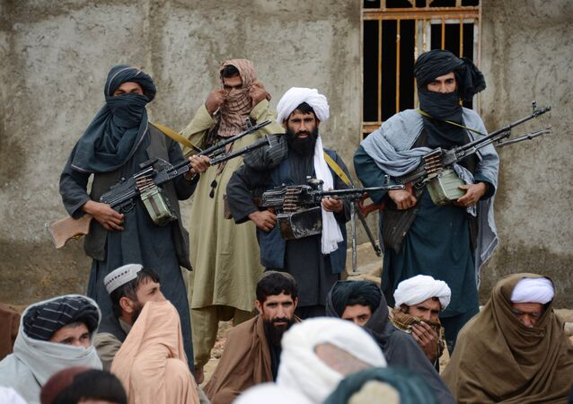 In this Tuesday, Nov. 3, 2015 photo, Afghan Taliban fighters listen to Mullah Mohammed Rasool, unseen, the newly-elected leader of a breakaway faction of the Taliban, in Farah province, Afghanistan