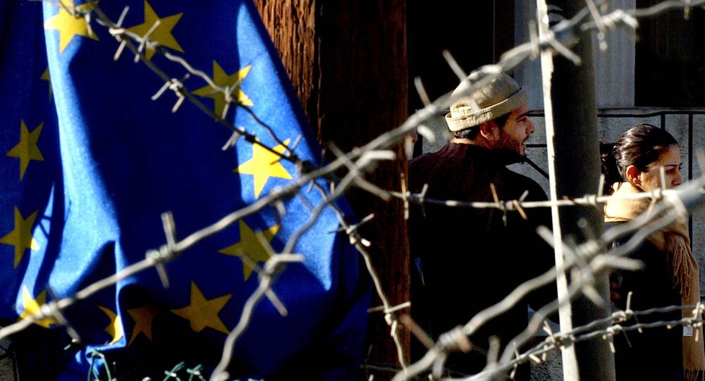 Turkish Cypriot couple, seen behind barbed wire and an EU flag, as they cross the Ledra Palace checkpoint in Nicosia, Cyprus.