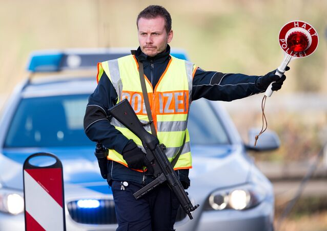 A policeman stops cars on highway 44 at a checkpoint in the Aachen, Germany