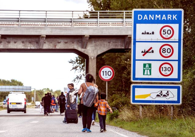 Migrants, who came from Germany by ferry and train Sunday night, walk from Rodby in southern Denmark towards Sweden on Monday Sept. 7, 2015.