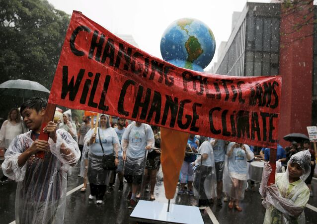 Indigenous boys hold a banner during a rally held the day before the start of the Paris Climate Change Conference (COP21), in Sao Paulo, Brazil, November 29, 2015