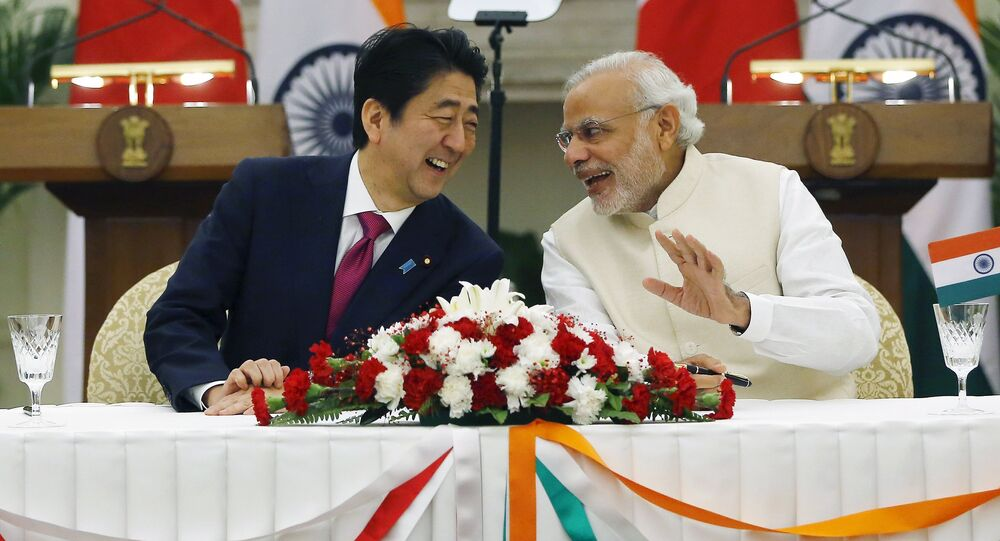 Japan's Prime Minister Shinzo Abe (L) and his Indian counterpart Narendra Modi shares a moment during a signing of agreement at Hyderabad House in New Delhi, India, December 12, 2015