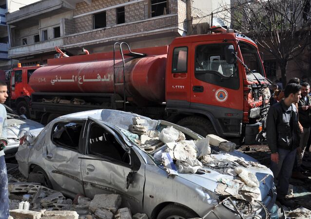 A firefighter truck is seen next to a destroyed car at the site of a car bomb explosion in al-Zahra neighborhood in Homs