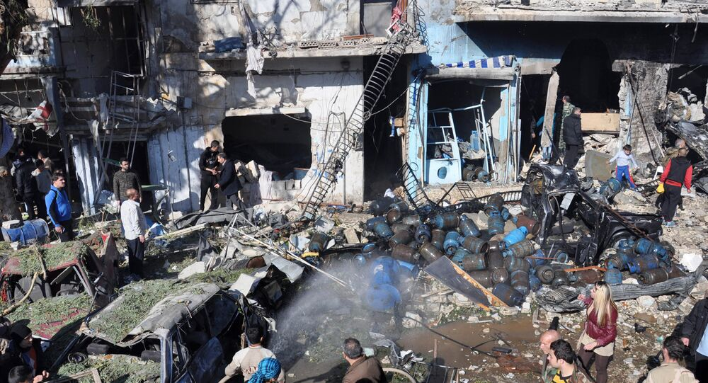 Syrians gather at the site of a car bomb explosion in al-Zahra neighborhood in Homs