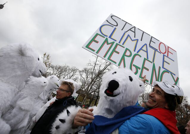 Jean-Baptiste Redde aka Voltuan holds a banner reading State of climate emergency next to demonstrators dressed-up as polar bears during a rally called by several Non Governmental Organisations (NGO) to form a human chain on the Champs de Mars near the Eiffel Tower in Paris on December 12, 2015 on the sidelines of the COP21, the UN conference on global warming.