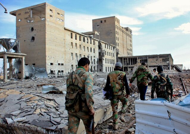 Syrian army soldiers patrol near a building previously used for storing seeds in the countryside of Deir Hafer, a former bastion of Islamic State group, near the northern Syrian city of Aleppo on December 2, 2015