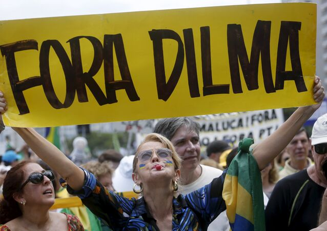 A demonstrator holds a banner which reads Out Dilma during a protest calling for the impeachment of Brazil's President Dilma Rousseff in Rio de Janeiro