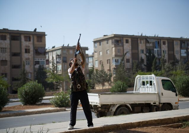 A Syrian rebel fighter fires his AK-47 rifle towards a Syrian army helicopter in Aleppo's Hanano district