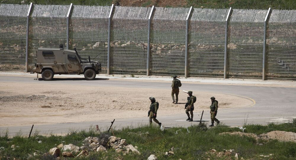 Israeli soldiers walk near a fence in the Israeli occupied Golan Heights on the border with war-torn Syria