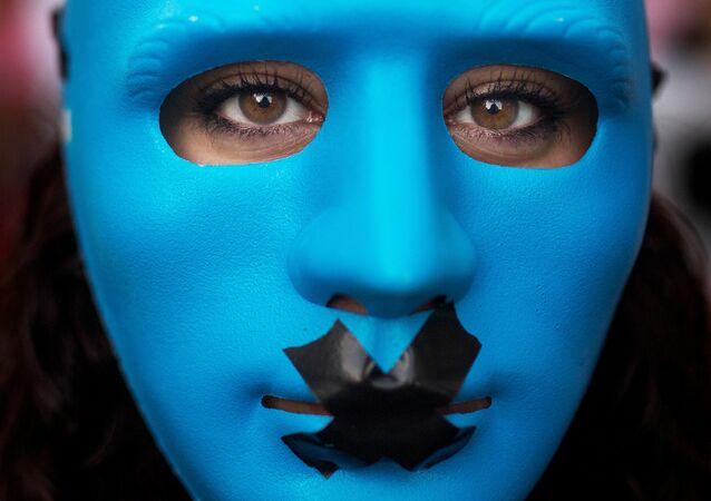 A protester wears a mask with a gag as she marches against the Public Security Law in Madrid, Spain, Tuesday, June 30, 2015.