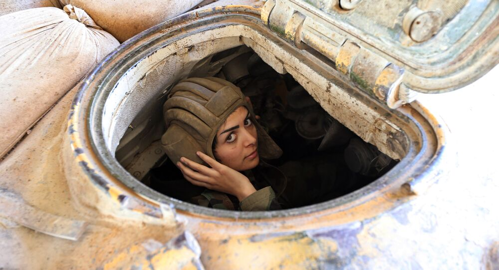 A female Syrian soldier from the Republican Guard commando battalion drives a tank during clashes with rebels in the restive Jobar area, in eastern Damascus