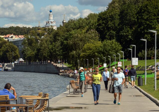People relax on the Moskva-river embankment on the territory of the Vorobyovy Gory Nature Park, Moscow