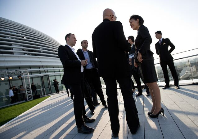 Soho China CEO Zhang Xin, second from right, chats with guests at her newly opened Galaxy Soho building in Beijing Saturday, Oct. 27, 2012.