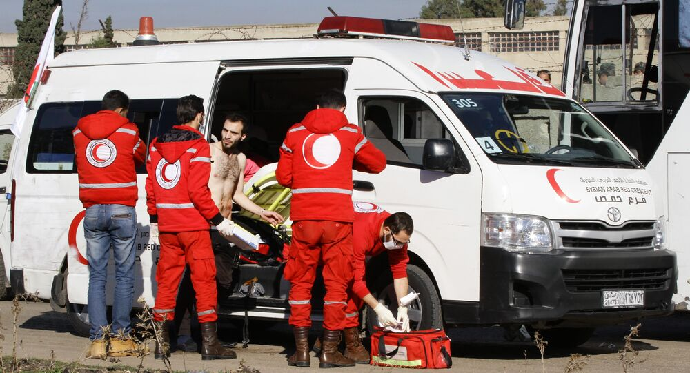 Members of the Syrian Red Crescent give aid to an injured man in the district of Waer in the central city of Homs on December 9, 2015 as hundreds of civilians and Syrian rebel forces began evacuating the last opposition-held district under a deal with the Syrian regime