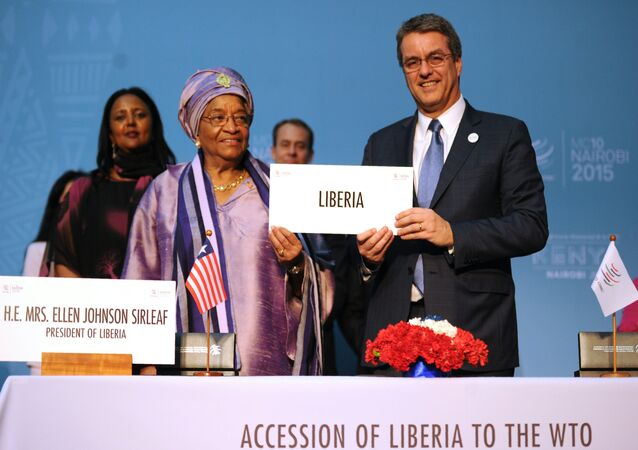 Liberian President Ellen Johnson-Sirleaf (L) holds up an identification plaque alongside World Trade Organisation (WTO) Director General Roberto Azevedo in Nairobi on December 16, 2015, during Liberia's accession to the WTO at the tenth ministerial conference
