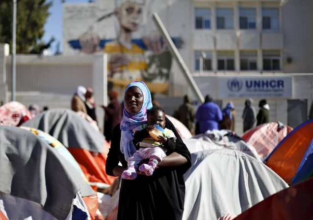 A Sudanese refugee from Darfur carries her child during an open-ended sit-in outside the United Nations High Commissioner for Refugees (UNHCR), demanding better treatment and acceleration of their relocation, in Amman, Jordan, December 6, 2015.