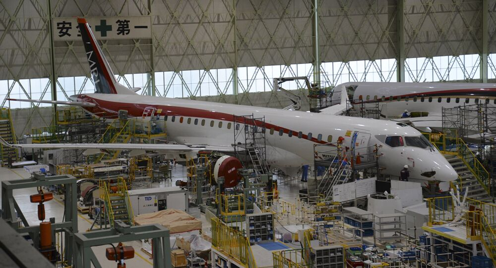 In this Friday, April 3, 2015 photo released by Mitsubishi Aircraft Corp., mechanics work on MRJ regional jet at the company's plant in Toyoyama, central Japan