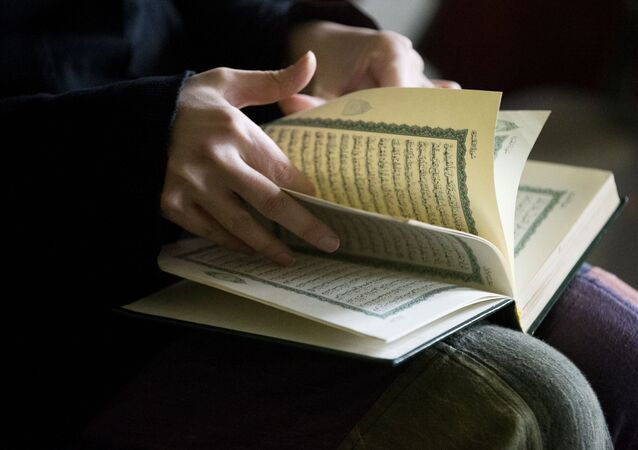 Syrian refugee, who agreed to be photograph on condition of anonymity because of fear of retaliation against family living in Syria, opens her Quran, Wednesday, Nov. 18, 2015