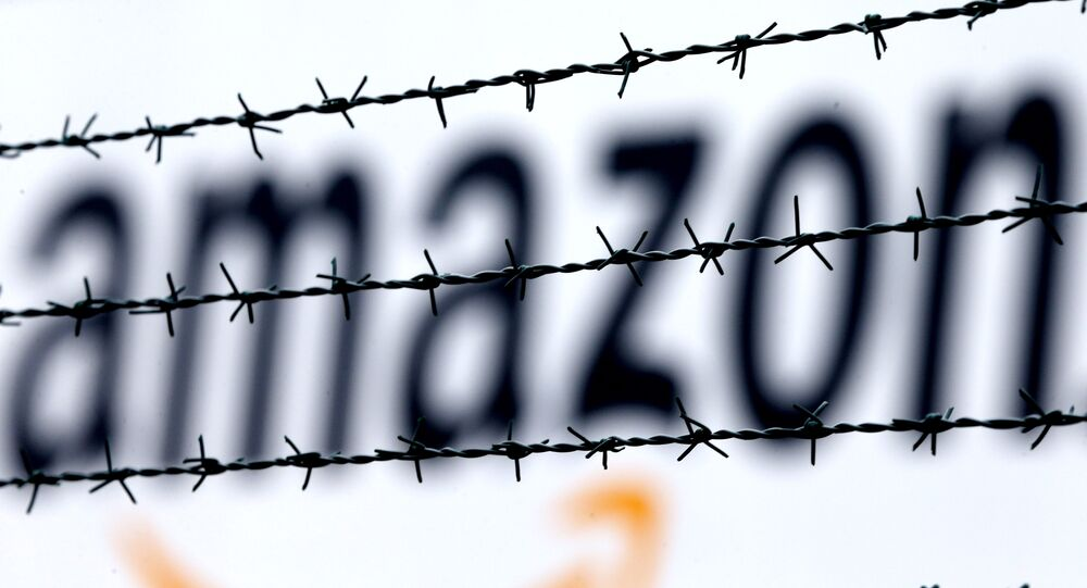 The internet trader Amazon logo is seen behind barbed wire at the company's logistic center in Rheinberg,Germany, Tuesday, Feb.19, 2013.